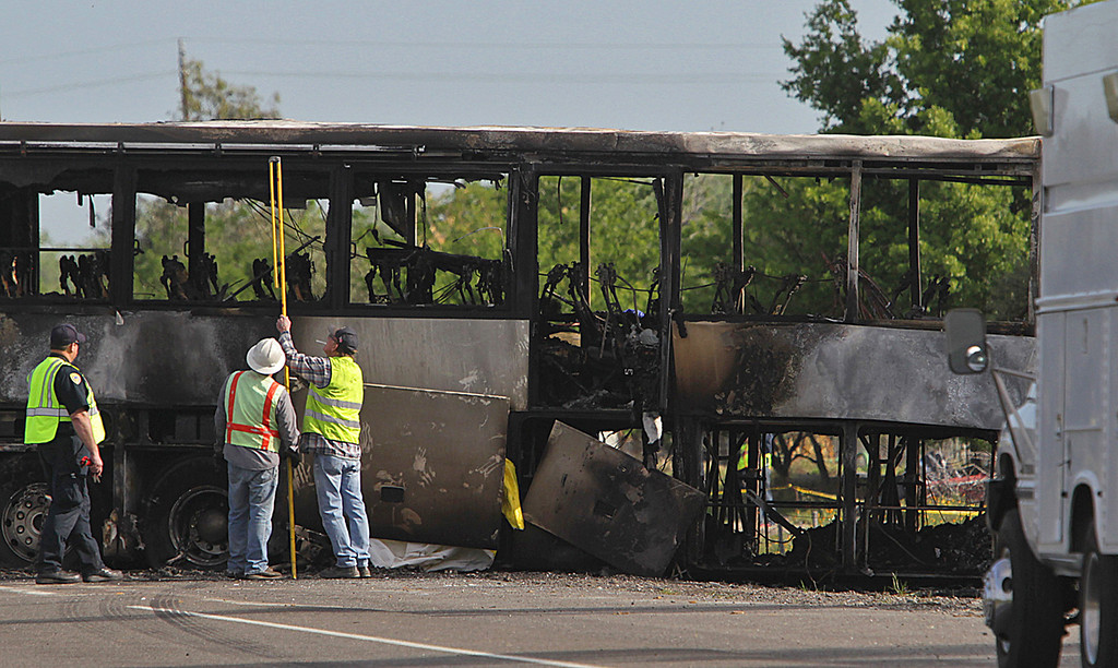 . Investigators look over the charred remains of a tour bus Friday, April 11, 2014, in Orland, Calif. At least ten people were killed and dozens injured on April 10, in the fiery crash on Interstate 5 between a Fed-Ex truck and the bus carrying high school students to visit to a Northern California college. (AP Photo/The Record Searchlight, Andreas Fuhrmann)