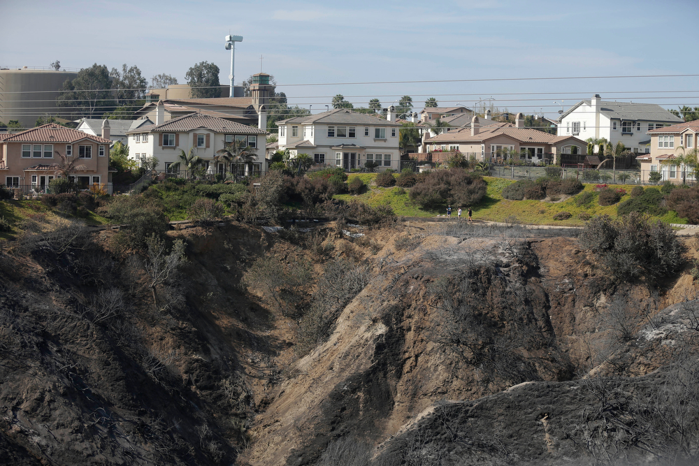 . Houses sit untouched above a canyon ravaged by wildfire Friday, May 16, 2014, in Carlsbad, Calif.  Some evacuation orders were lifted early Friday in an area near the fiercest of several wildfires in San Diego County, as crews building containment lines around the blazes hoped cooler temperatures will help them make further progress. (AP Photo/Gregory Bull)