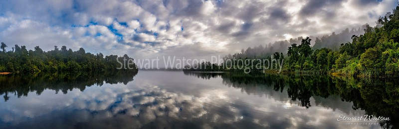 Cloud reflections on a misty morning of a bush and forest lined Lake Mapourika  in West Coast New Zealand