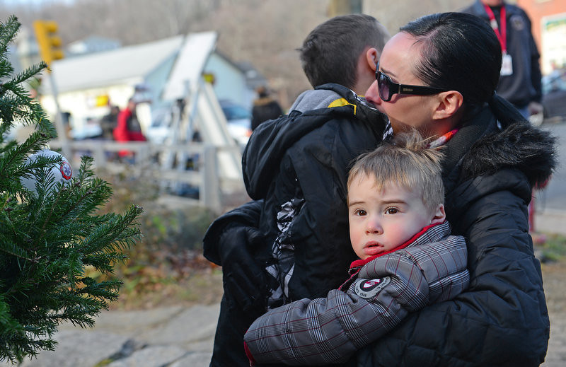 . A mother hugs her children after paying tribute to the victims of an elementary school shooting in Newtown, Connecticut, on December 15, 2012.  A young gunman slaughtered 20 small children and six teachers on December 14 after walking into a school in an idyllic Connecticut town wielding at least two sophisticated firearms.       EMMANUEL DUNAND/AFP/Getty Images