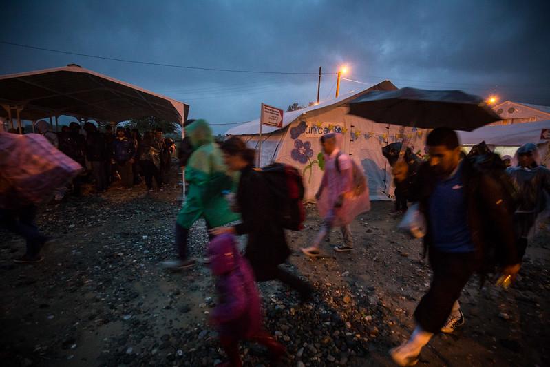 A group of refugees passes in front of the UNICEF tent in Gevglejia under heavy rain at night. Gevgelija, Macedonia. October 2015. ----------- Un groupe de réfugiés traverse le camp de transit de Gevgelija et passe devant la tente d'UNICEF durant la nuit et sous la pluie. Gevgelija, Macédoine. Octobre 2015.