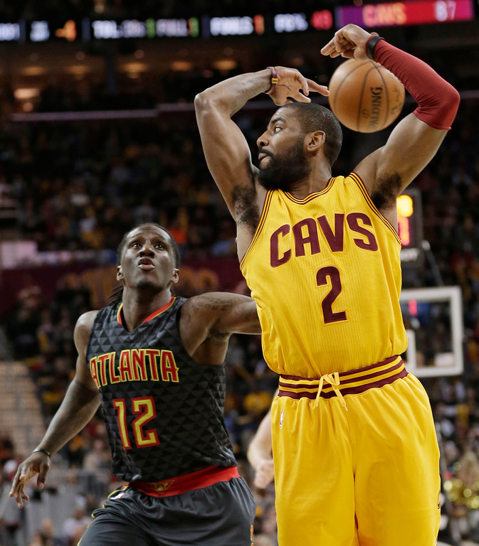 . Cleveland Cavaliers\' Kyrie Irving (2) passes behind his head against Atlanta Hawks\' Taurean Prince (12) in the second half of an NBA basketball game, Friday, April 7, 2017, in Cleveland. (AP Photo/Tony Dejak)