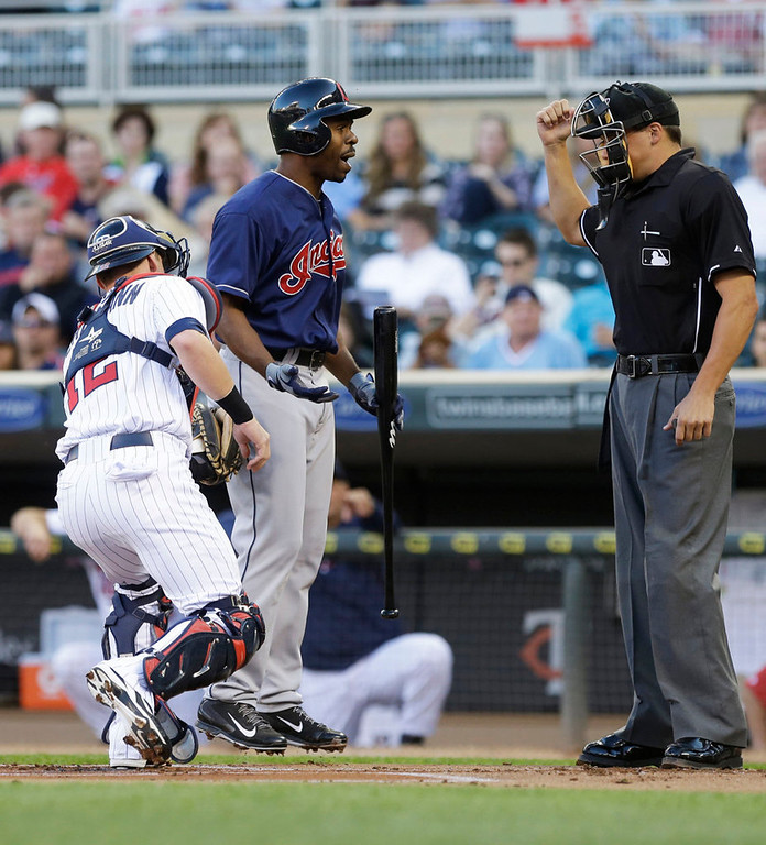 . Cleveland Indians\' Michael Bourn leaves the ground as he disputes a strikeout call by plate umpire Adam Hamari and Minnesota Twins catcher Chris Herrmann makes the tag in the first inning. (AP Photo/Jim Mone)