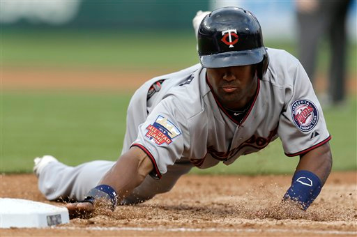 . Minnesota Twins\' Danny Santana dives safely back into first base against the Detroit Tigers in the third inning of a baseball game in Detroit, Friday, June 13, 2014.  (AP Photo/Paul Sancya)