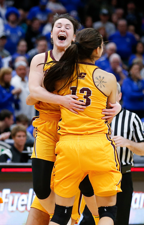 . Central Michigan guard Presley Hudson and Reyna Frost (13) celebrate after defeating Buffalo 96-91 in an NCAA college basketball game during the championship of the Mid-American Conference tournament Saturday, March 10, 2018, in Cleveland. (AP Photo/Ron Schwane)