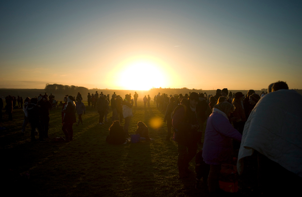 Description of . Revellers gather as they enjoy the sunrise during the winter solstice at Stonehenge on Salisbury Plain in southern England December 21, 2012. The winter solstice is the shortest day of the year, and the longest night of the year. REUTERS/Kieran Doherty