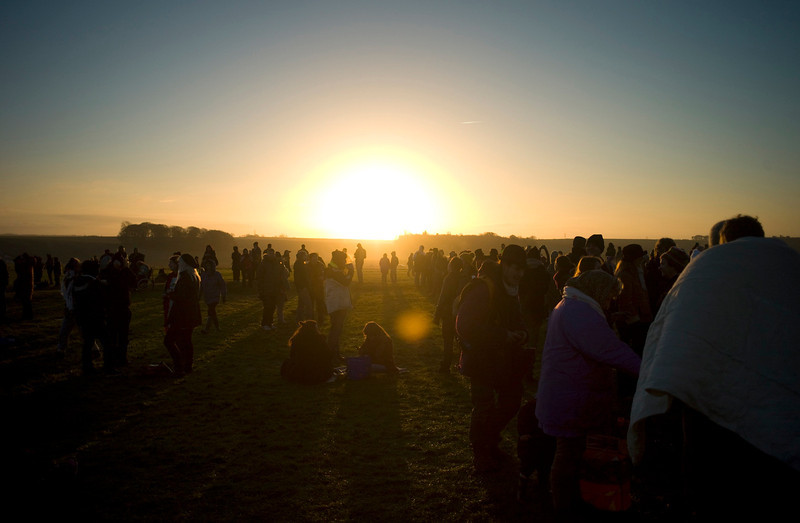 . Revellers gather as they enjoy the sunrise during the winter solstice at Stonehenge on Salisbury Plain in southern England December 21, 2012. The winter solstice is the shortest day of the year, and the longest night of the year. REUTERS/Kieran Doherty