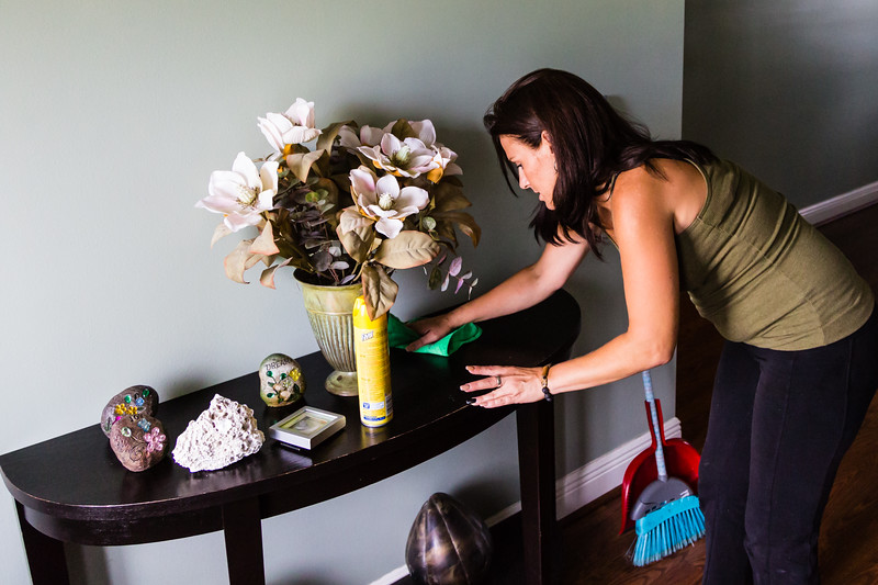 """Amy Kilgore, 37, of Philadelphia, Pennsylvania cleans the side table in the foyer at the All About Recovery younger women's sober home in Loxahatchee, Florida on Friday, June 24, 2016. Residents are required to keep the sober home clean, but once a week, the residents  are assigned an area of the sober house to """"deep clean"""". (Joseph Forzano / The Palm Beach Post)"""