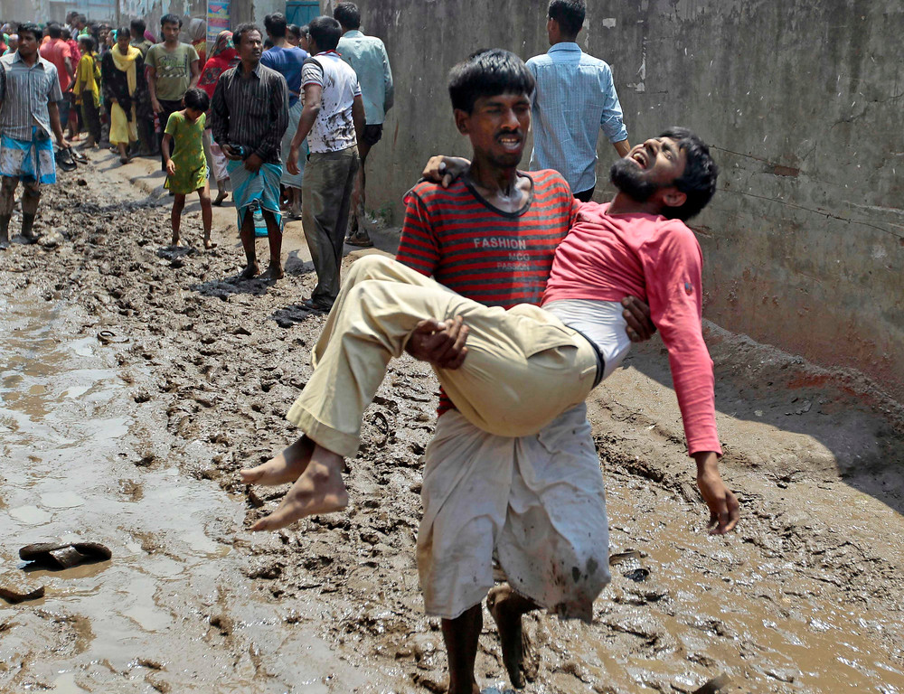 . A survivor reacts in pain as he is carried by a rescuer after an eight-story building housing several garment factories collapsed in Savar, near Dhaka, Bangladesh, Wednesday, April 24, 2013. (AP Photo/ A.M. Ahad)