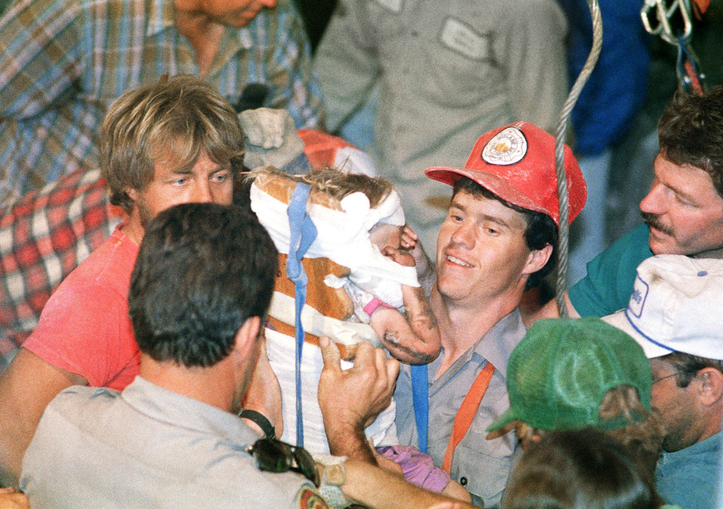 . Rescue worker Steven Forbes carries 18-month-old Jessica McClure after she was rescued from abandoned water well in Midland, Texas, Oct. 16, 1987. (AP Photo/Eric Gay)