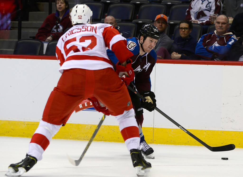 . DENVER, CO - February 5: Colorado Avalanche left wing Cody McLeod (55) looks for a passing lane around Detroit Red Wings defenseman Jonathan Ericsson (52) during the third period Thursday, February 5, 2015 at the Pepsi Center in Denver, Colorado. The Avalanche lost 3-0 to the Red Wings. (Photo By Brent Lewis/The Denver Post)