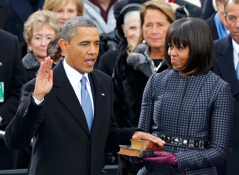 Description of . U.S. President Barack Obama recites his oath of office as first lady Michelle Obama looks on during swearing-in ceremonies on the West front of the U.S Capitol in Washington, January 21, 2013. REUTERS/Jim Bourg