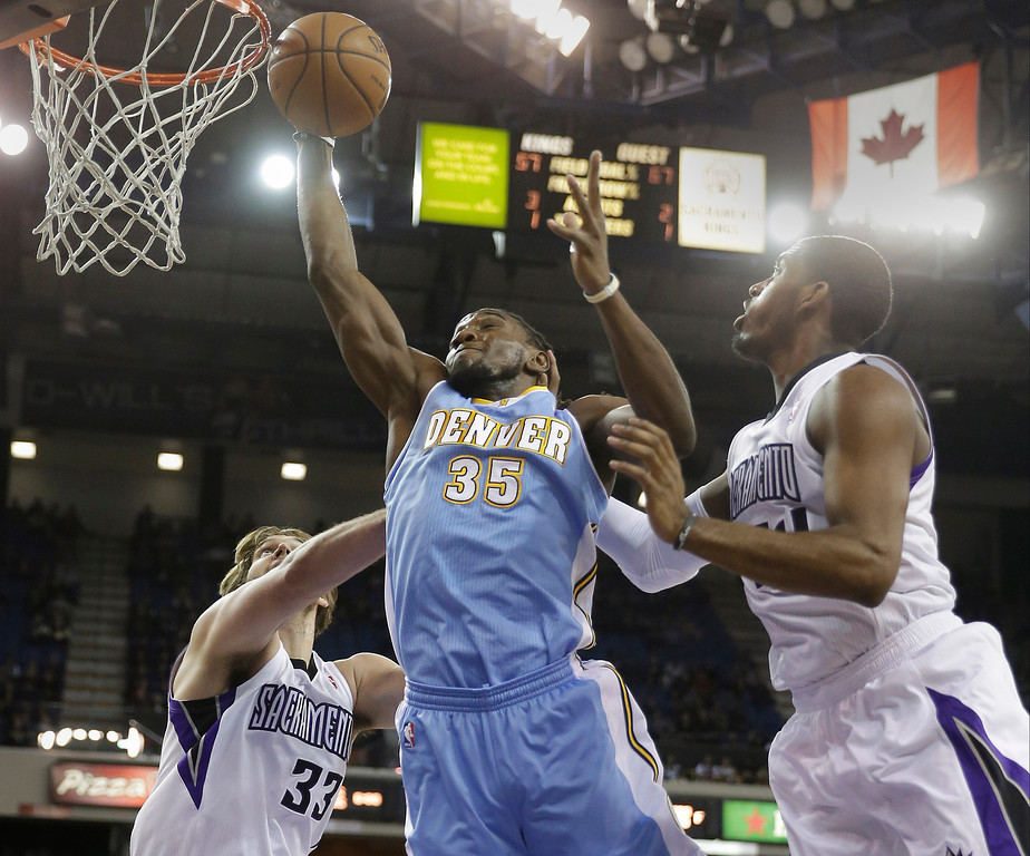 . Denver Nuggets forward Kenneth Faried, center, grabs a rebound between Sacramento Kings\' Aaron Gray, left, and Jason Thompson during the first quarter of an NBA basketball game in Sacramento, Calif., Sunday, Jan. 26, 2014. (AP Photo/Rich Pedroncelli)