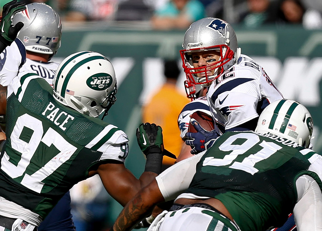 . Tom Brady #12 of the New England Patriots tries to shake Sheldon Richardson #91 and Calvin Pace #97 of the New York Jets during their game at MetLife Stadium on October 20, 2013 in East Rutherford, New Jersey.  (Photo by Jeff Zelevansky/Getty Images)