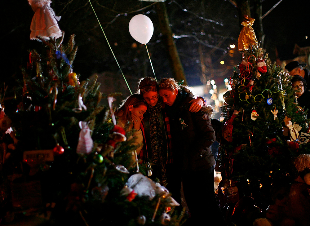 Description of . People are seen at a makeshift memorial in Newtown, Connecticut December 17, 2012. Two funerals on Monday ushered in what will be a week of memorial services and burials for the 20 children and six adults massacred in a shooting at Sandy Hook Elementary School in Newtown last Friday. REUTERS/Eric Thayer