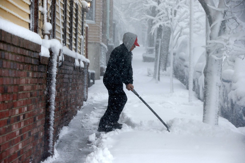 . Afonso Siciliano clears snow on Cottage Street in Boston, Tuesday, March 13, 2018. Boston finds itself in the bullseye of the third nor\'easter in two weeks, with forecasters warning of up to 18 inches of snow and 2 feet or more to the south. (AP Photo/Michael Dwyer)