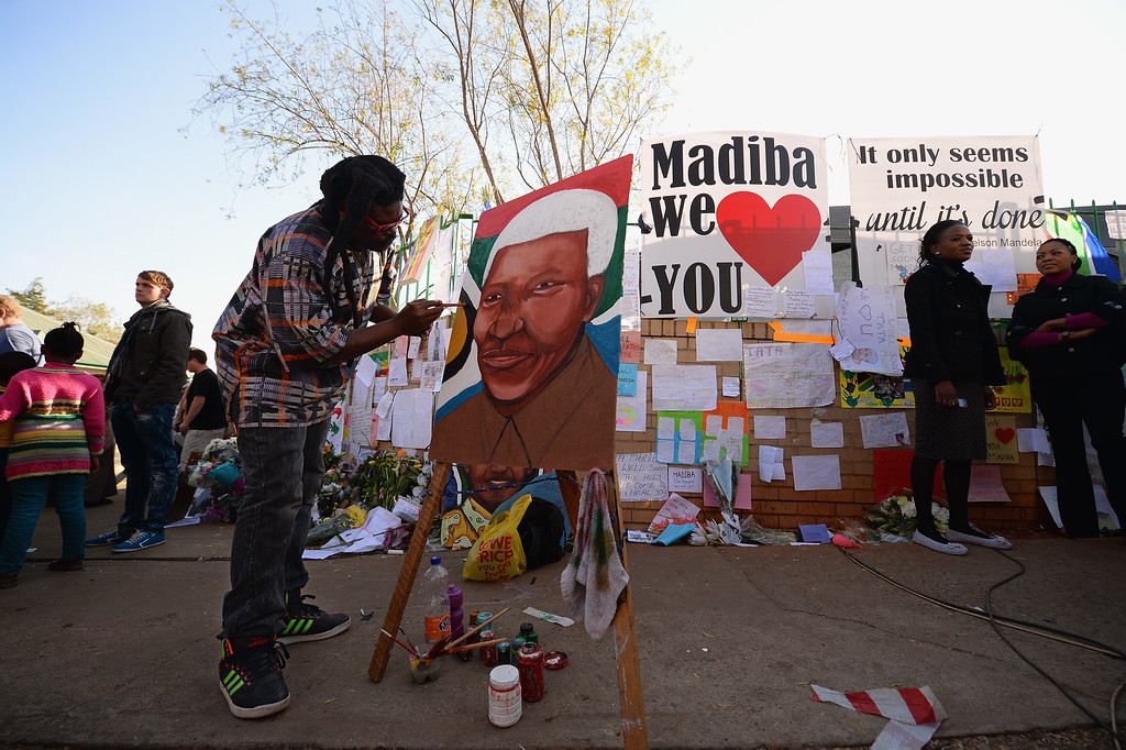 . PRETORIA, SOUTH AFRICA - JUNE 26:  A man paints a picture as people gather to leave messages of support for former South African President Nelson Mandela outside the Mediclinic Heart Hospital June 26, 2013 in Pretoria, South Africa. South African President Jacob Zuma confirmed on June 23 that Mandela\'s condition has become critical since he was admitted to the hospital over two weeks ago for a recurring lung infection.  (Photo by Jeff J Mitchell/Getty Images)