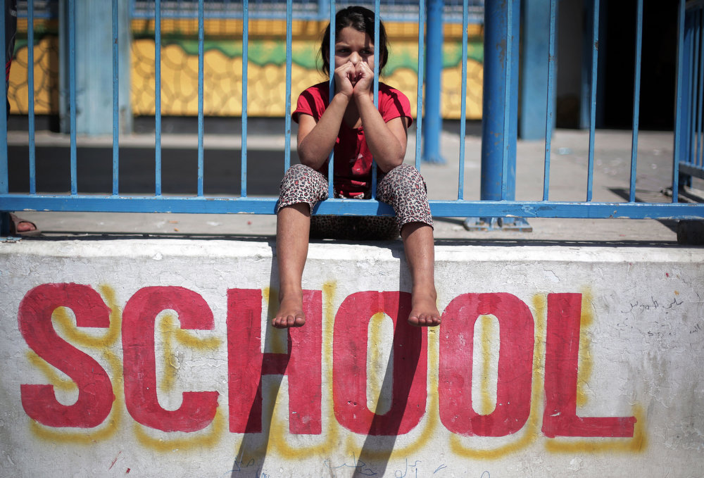 . In this Monday, July 14, 2014 photo, a Palestinian girl sits on the wall of the New Gaza United Nations School, where dozens of families have sought refuge after fleeing their home in fear of Israeli airstrikes. 20 U.N. schools took in more than 17,000 displaced Gazans, many of them children, after Saturday\'s warnings by Israel that civilians must clear out of northern Gaza. (AP Photo/Khalil Hamra)