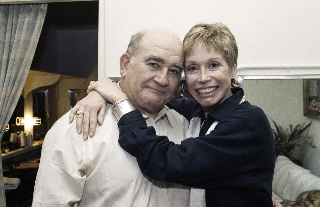 . Mary Tyler Moore hugs Ed Asner as she pays a visit backstage, Thursday, March 17, 1989 at the 46th Street Theatre in New York where Asner is starring in ?Bonn Yesterday.? Moore and Asner starred in the long-running television it ?The Mary Tyler Moore Show.? (AP Photo/Ron Frehm)