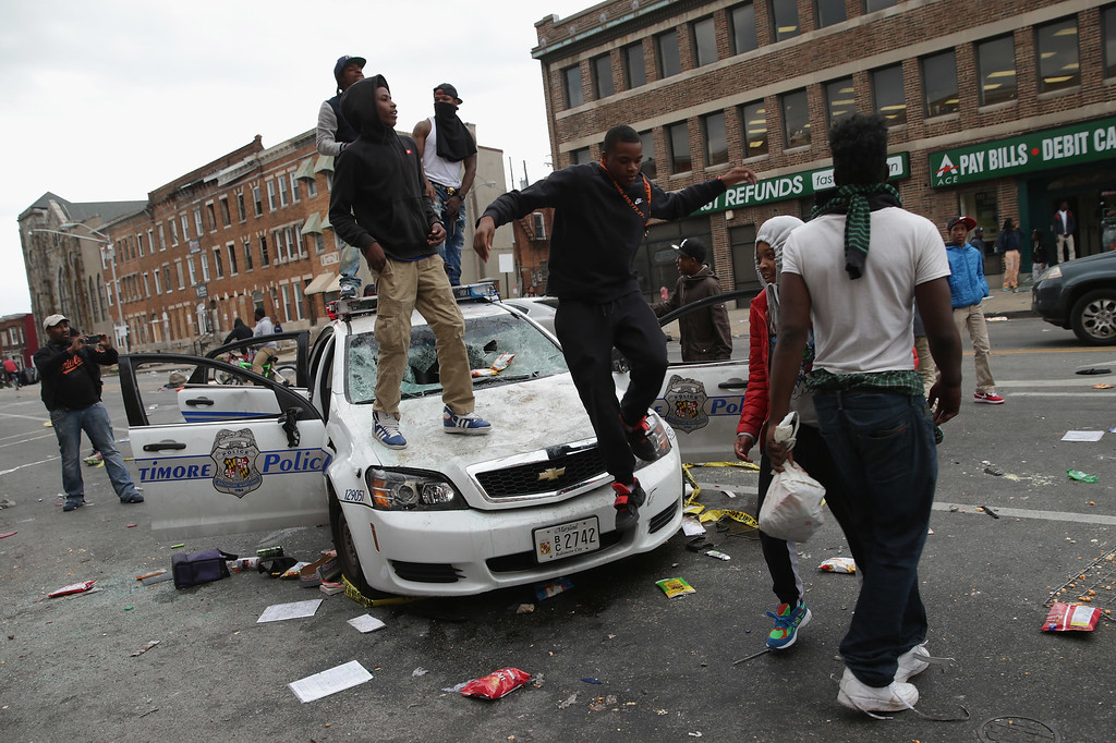 . BALTIMORE, MD - APRIL 27:  Demonstrators climb on a destroyed Baltimore Police car in the street near the corner of Pennsylvania and North avenues during violent protests following the funeral of Freddie Gray April 27, 2015 in Baltimore, Maryland. Gray, 25, who was arrested for possessing a switch blade knife April 12 outside the Gilmor Homes housing project on Baltimore\'s west side. According to his attorney, Gray died a week later in the hospital from a severe spinal cord injury he received while in police custody.  (Photo by Chip Somodevilla/Getty Images)
