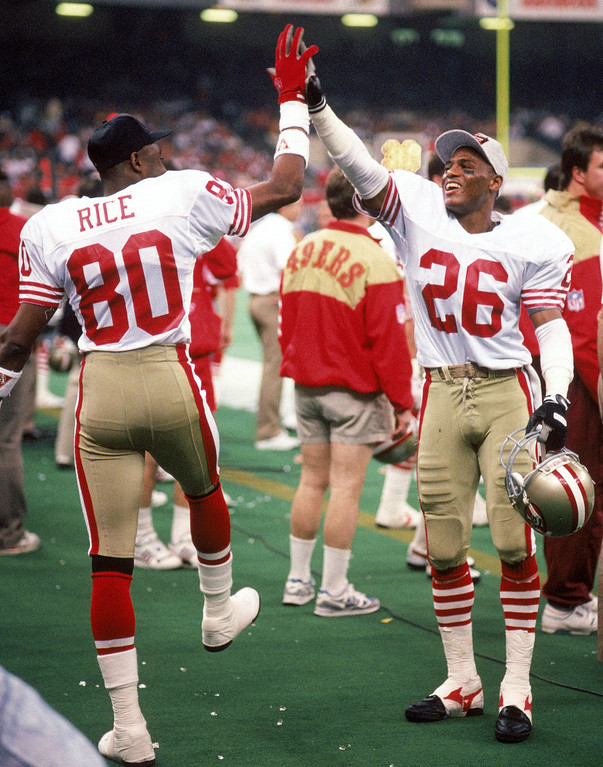 . Wide receiver New York Giants #80 and cornerback Darryl Pollard #26 of the San Francisco 49ers celebrate on the sideline in Super Bowl XXIV against the Denver Broncos at Louisiana Superdome on January 28, 1990 in New Orleans, Louisiana.  The 49ers won 55-10.  (Photo by George Rose/Getty Images)