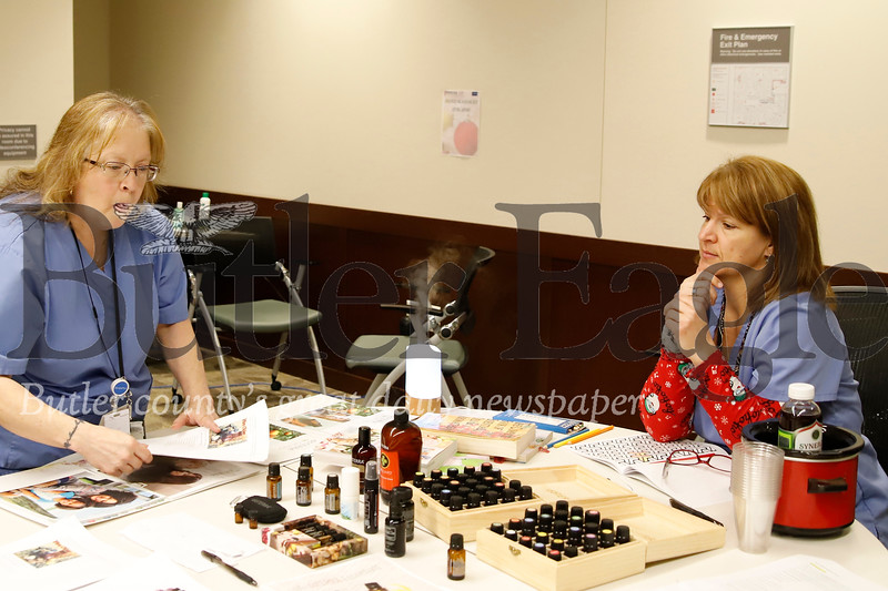 Butler VA registered nurse and DoTerra consultant Caroline Roxberry (right) discusses aromatherapy fragrances with VA pharmacy tech Brenda Rivera at the VA's stress relief workshop Thursday. Seb Foltz/Butler Eagle