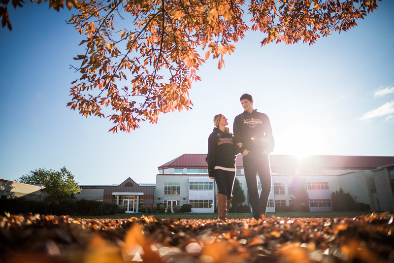 A girl and a man walking together while holding arms on campus.