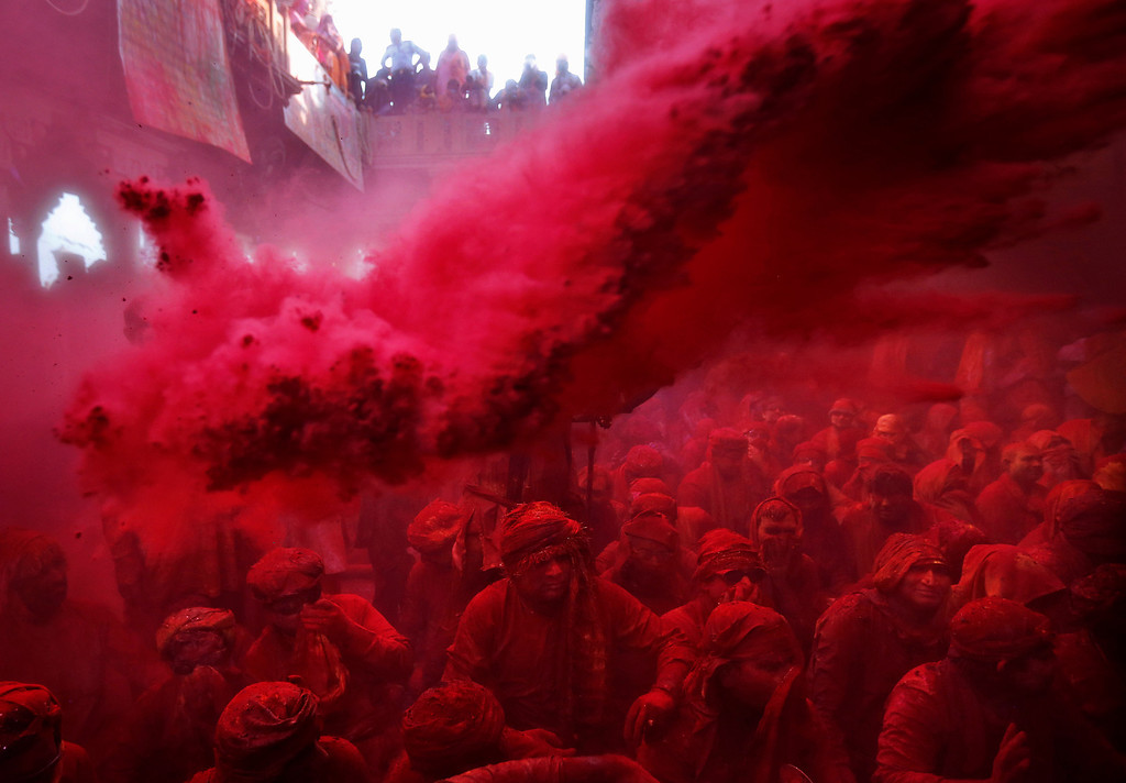 . Colored powder is thrown on Hindu men from the village of Nandgaon as they sit on the floor during prayers at the Ladali or Radha temple before the procession for the Lathmar Holy festival, the legendary hometown of Radha, consort of Hindu God Krishna, in Barsana, 115 kilometers (71 miles) from New Delhi, India, Thursday, March 21, 2013. During Lathmar Holi the women of Barsana beat the men from Nandgaon, the hometown of Krishna, with wooden sticks in response to their teasing as they depart the town. (AP Photo/Kevin Frayer)