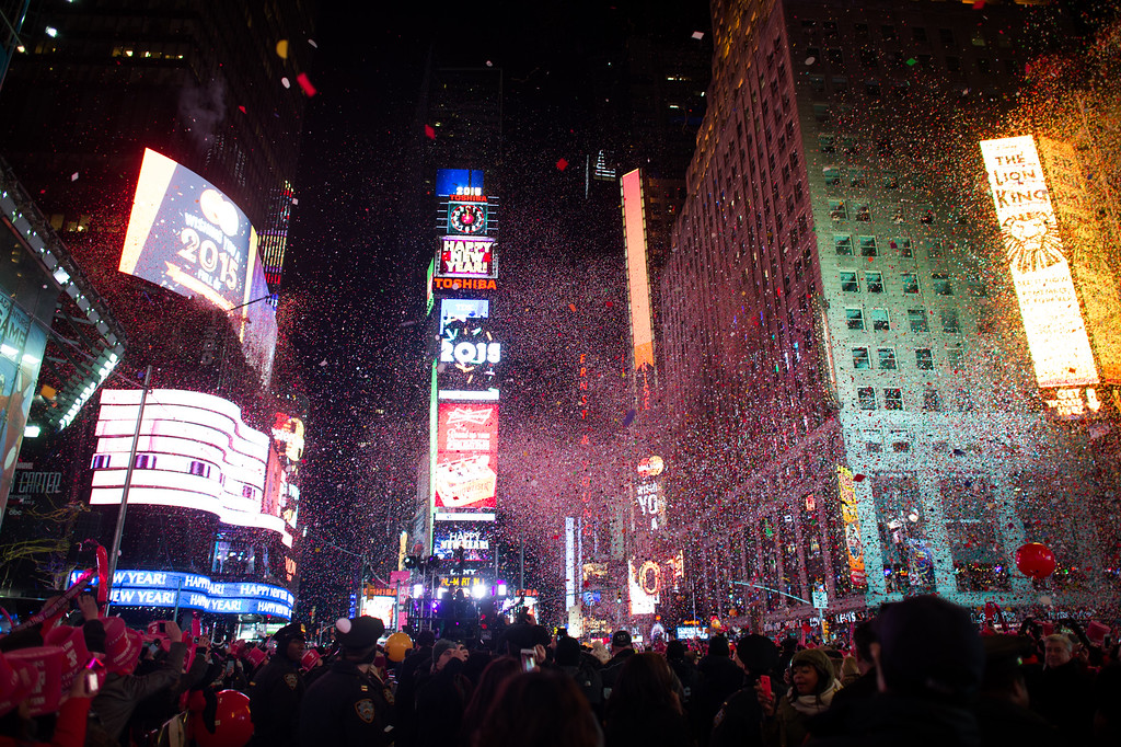 . NEW YORK, NY - JANUARY 1:  People cheer as the ball drops at midnight in Times Square on January 1, 2015 in New York City. An estimated one million people from around the world are expected to pack Times Square to ring in 2015. (Photo by Andrew Theodorakis/Getty Images)