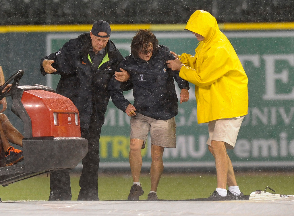 . Detroit Tigers head groundskeeper Heather Nabozny, center, is helped to her feet by ground personnel after injuring herself while helping put the rain tarp on the field during a rain delay in a baseball game between the Tigers and the San Francisco Giants in the fourth inning Friday, Sept. 5, 2014, in Detroit. (AP Photo/Jose Juarez)