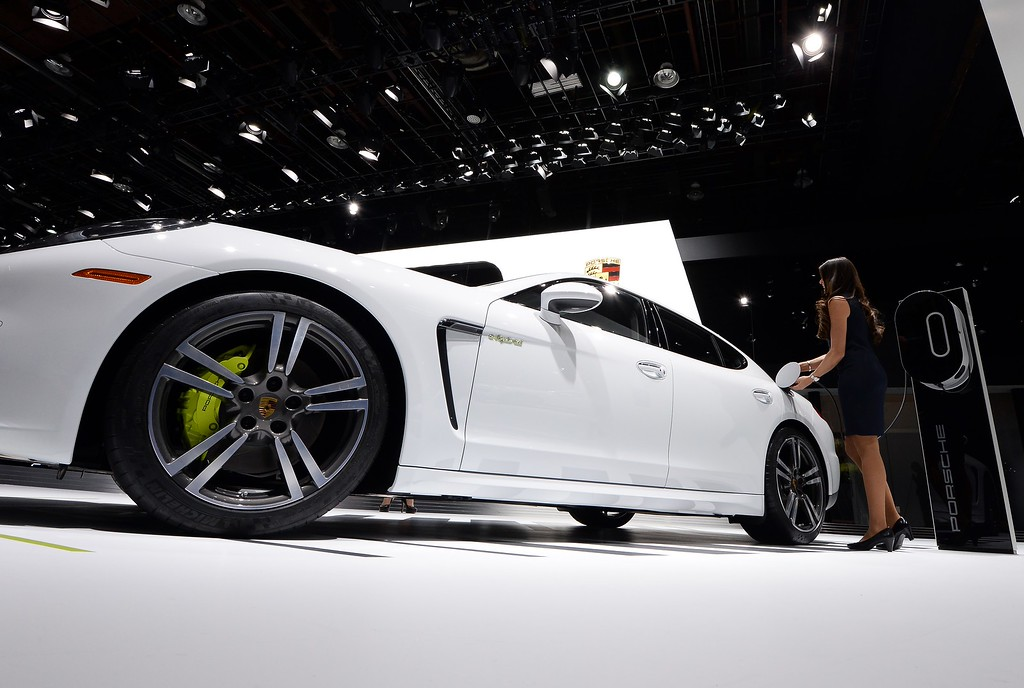 . A woman connects the Porsche Panamera S to charge during the press preview of the 2016 North American International Auto Show in Detroit, Michigan, on January 12, 2016. AFP PHOTO/JEWEL SAMAD/AFP/Getty Images