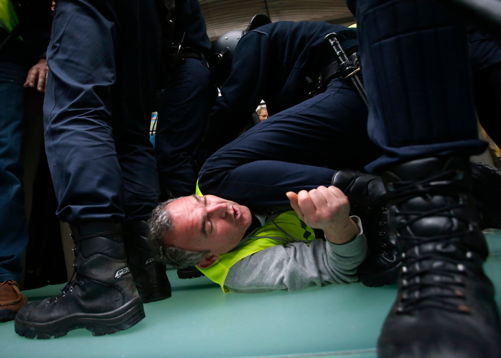Description of . An Iberia worker is arrested by Spanish riot police officers during clashes at Madrid's Barajas airport February 18, 2013. Workers at loss-making Spanish flag carrier Iberia began a five-day strike at midnight on Monday, grounding over 1,000 flights and costing the airline and struggling national economy millions of euros. REUTERS/Sergio Perez