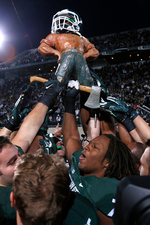 . Michigan State players celebrate with the Paul Bunyon trophy following their 35-11 win over Michigan in an NCAA college football game, Saturday, Oct. 25, 2014, in East Lansing, Mich. (AP Photo/Al Goldis)