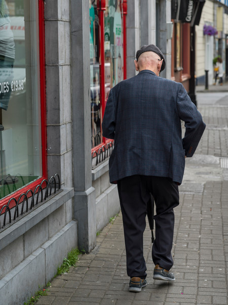Rear view of senior man walking on street, Galway City, County Galway, Ireland