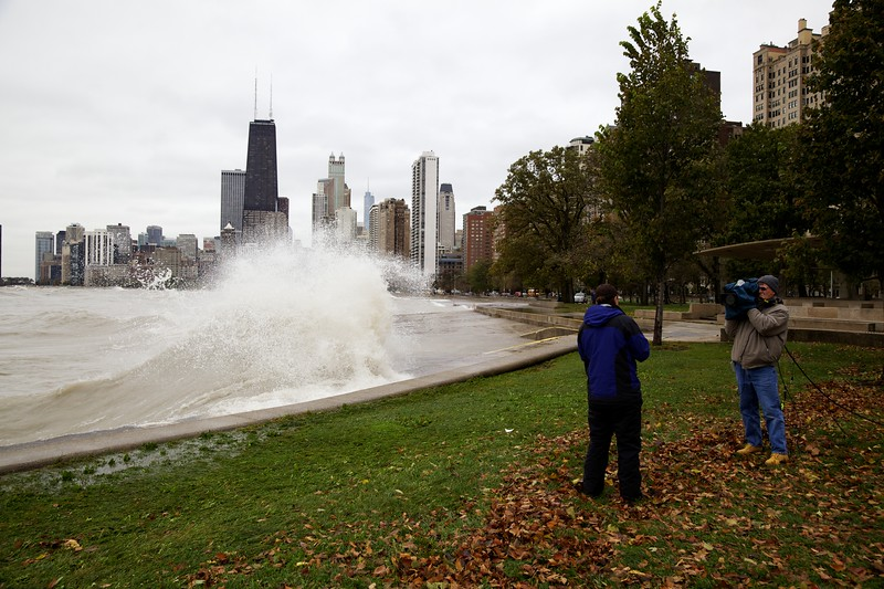 Television reporter and cameraman on Chicago lakefront reporting on large waves.
