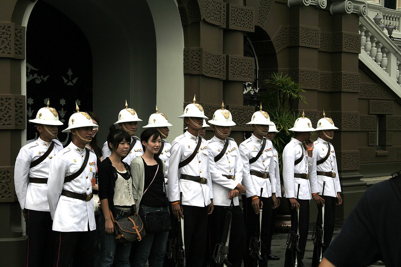 Guards at the Grand Palace pose with some overly excited tourist girls.