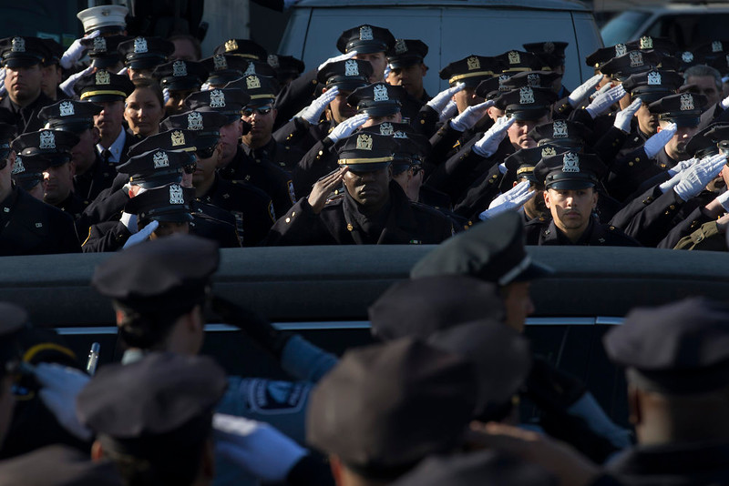 . Police officers salute as the hearse of New York city police officer Rafael Ramos drives along his funeral procession route in the Glendale section of Queens, Saturday, Dec. 27, 2014, in New York. Ramos and his partner, officer Wenjian Liu, were killed Dec. 20 as they sat in their patrol car on a Brooklyn street. The shooter, Ismaaiyl Brinsley, later killed himself. (AP Photo/John Minchillo)