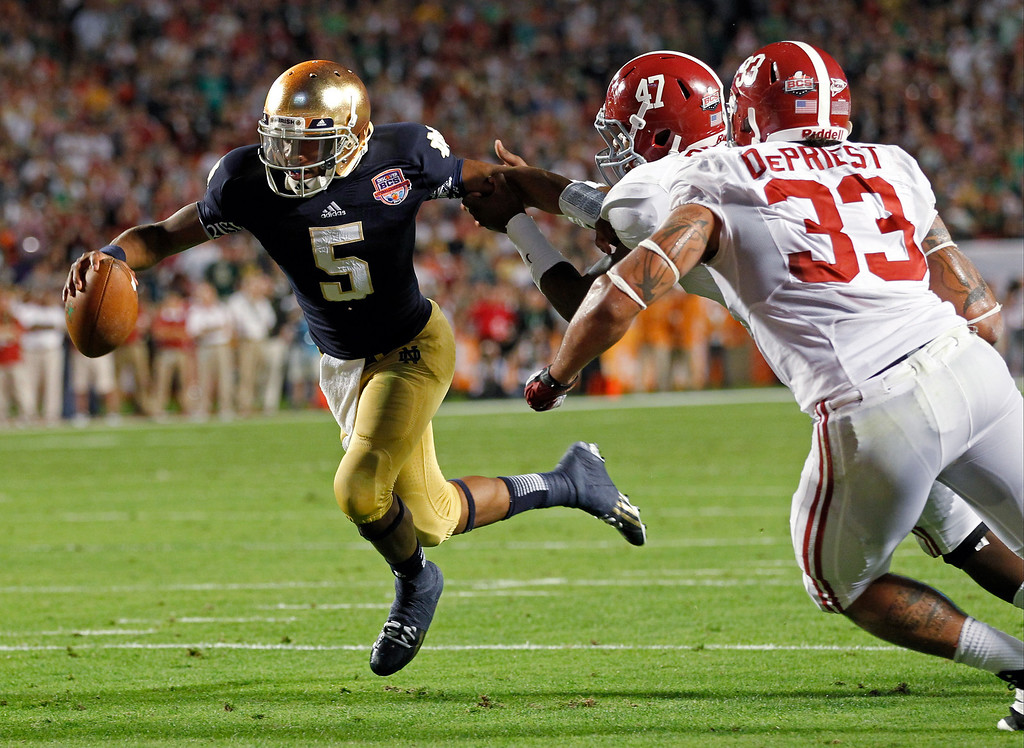 . Notre Dame quarterback Everett Golson (5) runs past Alabama\'s Xzavier Dickson (47) and Trey DePriest (33) for a touchdown during the second half of the BCS National Championship college football game Monday, Jan. 7, 2013, in Miami. (AP Photo/Wilfredo Lee)