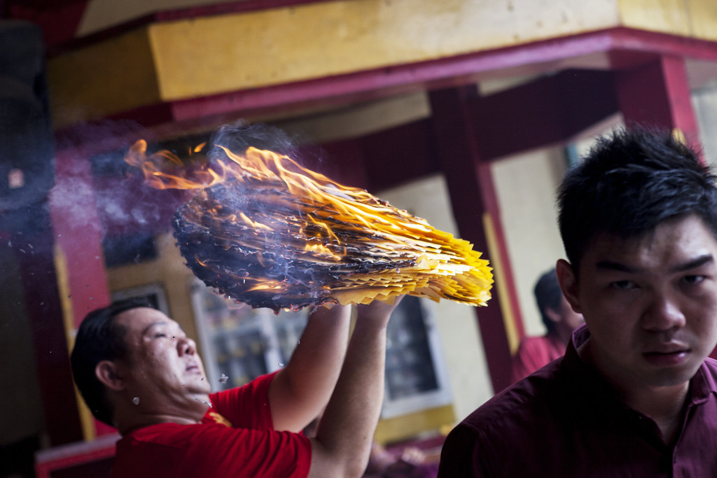 . A man holds votive paper and burns it as they attend prayers during Chinese New Year celebrations for the Year of The Horse at Bun San Bio Temple on January 31, 2014 in Tangerang, Indonesia.  (Photo by Oscar Siagian/Getty Images)