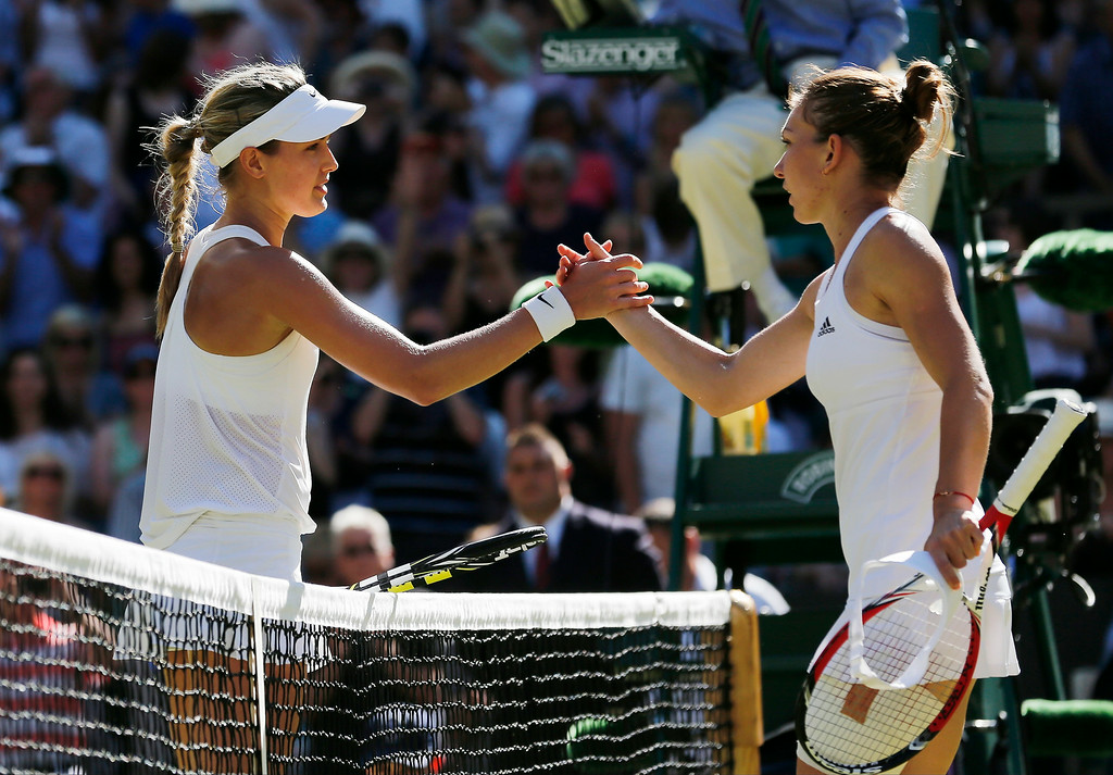 . Eugenie Bouchard of Canada shakes hands after defeating Simona Halep of Romania, right, in the women\'s singles semifinal match at the All England Lawn Tennis Championships in Wimbledon, London, Thursday July 3, 2014. (AP Photo/Ben Curtis)