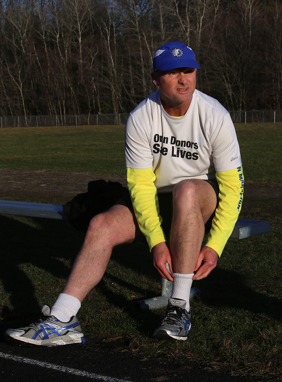 . Donald Davis, 54, of Reading, who will run the Boston Marathon route Sunday a week early to raise money for DonateLife and promote organ and tissue donation, gets ready for a short run at the Marshall Middle School track with his nephew, who will run with him forwards. (SUN/Julia Malakie)
