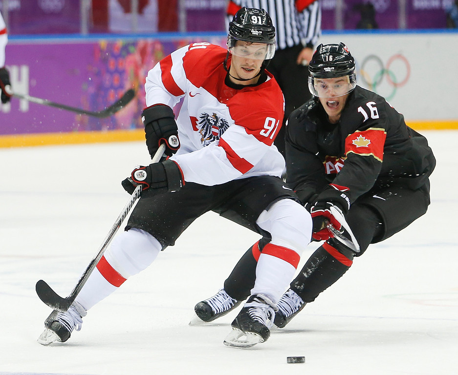 . Austria forward Oliver Setzinger, left, and Canada forward Jonathan Toews vie for the puck in the second period of a men\'s ice hockey game at the 2014 Winter Olympics, Friday, Feb. 14, 2014, in Sochi, Russia. (AP Photo/Mark Humphrey)