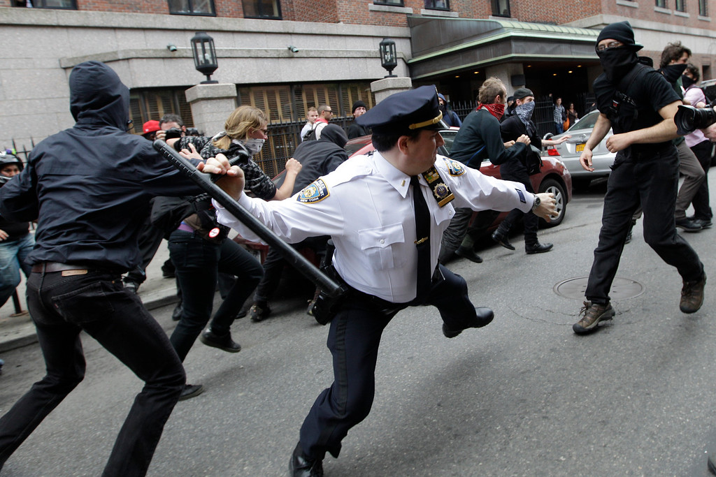 . In this May 1, 2012 file photo, a police lieutenant swings his baton at Occupy Wall Street activists in New York.  Hundreds of activists with a variety of causes spread out over New York City on International Workers Day, or May Day, with Occupy Wall Street members leading a charge against financial institutions. (AP Photo/Mary Altaffer, File)