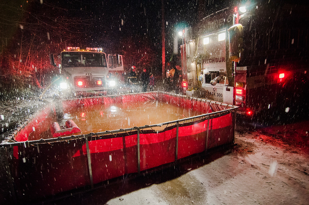 . Crews take in water from neighboring towns to battle a three-alarm fire at 17 Birchwood Terrace in Ashburnham on Tuesday evening. SENTINEL & ENTERPRISE / Ashley Green