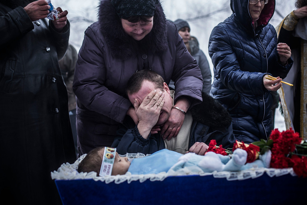 . Vladimir Bovrichev, 30, cries next to the body of his son Artiam, 4, killed in a Ukrainian army artillery strike, during his funeral in Kuivisevsky district on the outskirts of Donetsk, eastern Ukraine, Tuesday, Jan. 20, 2015. At least three civilians were killed in shelling Tuesday in eastern Ukraine as fighting continued between government and rebel forces in the separatist-held city of Donetsk. (AP Photo/Manu Brabo)