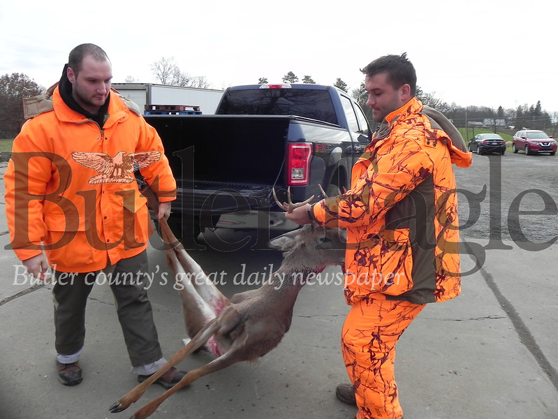 Kevin Lesniak (left) carries a buck that his brother, Ben Lesniak (right), shot on Saturday's opening day. They delivered the deer to Cabot's McKruit Custom Meat Cutting for processing.
