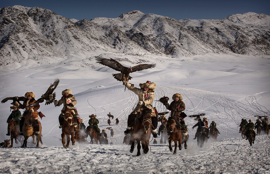 . Chinese Kazakh eagle hunters ride with their eagles during a local competition on January 30, 2015 in the mountains of Qinghe County, Xinjiang, northwestern China. The festival, organized by the local hunting community, is part of an effort to promote and grow traditional hunting practices for new generations in the mountainous region of western China that borders Kazakhstan, Russia and Mongolia. The training and handling of the large birds of prey follows a strict set of ancient rules that Kazakh eagle hunters are preserving for future generations.  (Photo by Kevin Frayer/Getty Images)