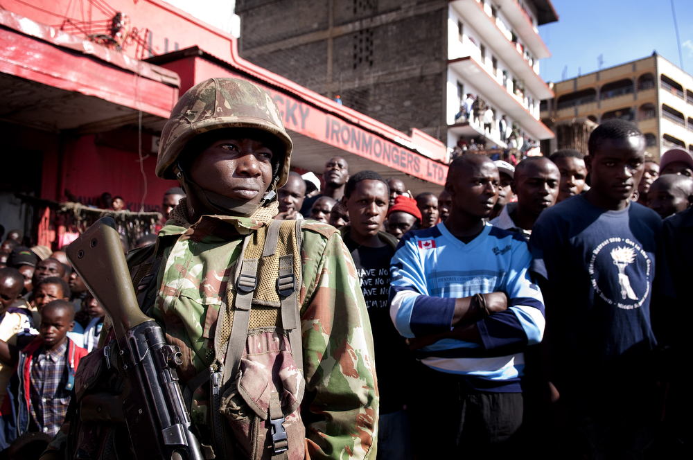 . A soldier in the Kenya Defense Forces (KDF) keeps control of onlookers after two improvised explosive devices (IED) went off in Gikomba market on May 16, 2014 in Nairobi, Kenya. Two improvised explosive devices (IED) were activated, killing several people and injuring more than 70. One person has been apprehended as a suspect in the attack. (Photo by Christena Dowsett/Getty Images)