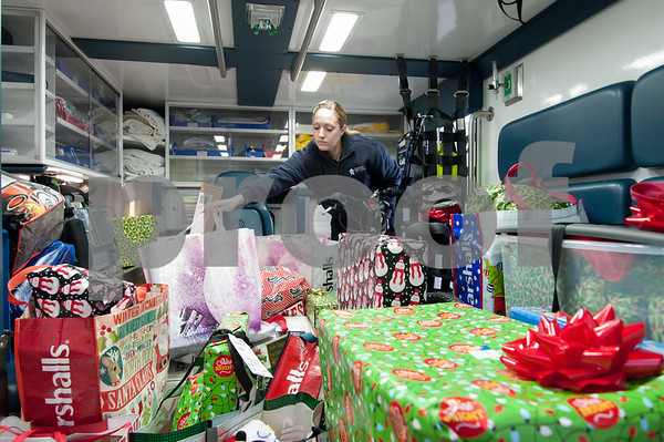 12/21/17 Wesley Bunnell | Staff New Britain Emergency Services Kristen Farrell loads the last of the gifts onto an ambulance as part of the 3rd annual New Britain EMS Stuff A Truck w which matches families with children who are part of The Friendship Center's housing and sheltering programs. This year's program was partnered with the Hospital of Central Connecticut and the New Britain Fire Department.