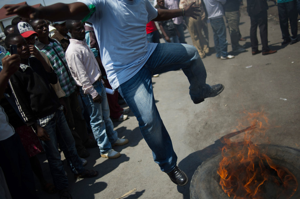 Description of . A Congolese demonstrator jumps over a burning tyre in Goma on December 6, 2012 as a small group of youth activists demonstrates, protesting the inaction of the UN and the government, after M23 rebels took the city on November 20. Rebels in the Democratic Republic of Congo will start talks with Kinshasa's government in Kampala on December 7, to